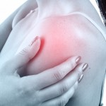 A woman rubbing her painful Shoulder