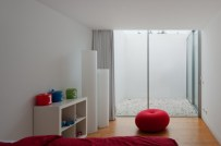 white-cube-bookcase-design-and-red-beanbags-above-wooden-flooring