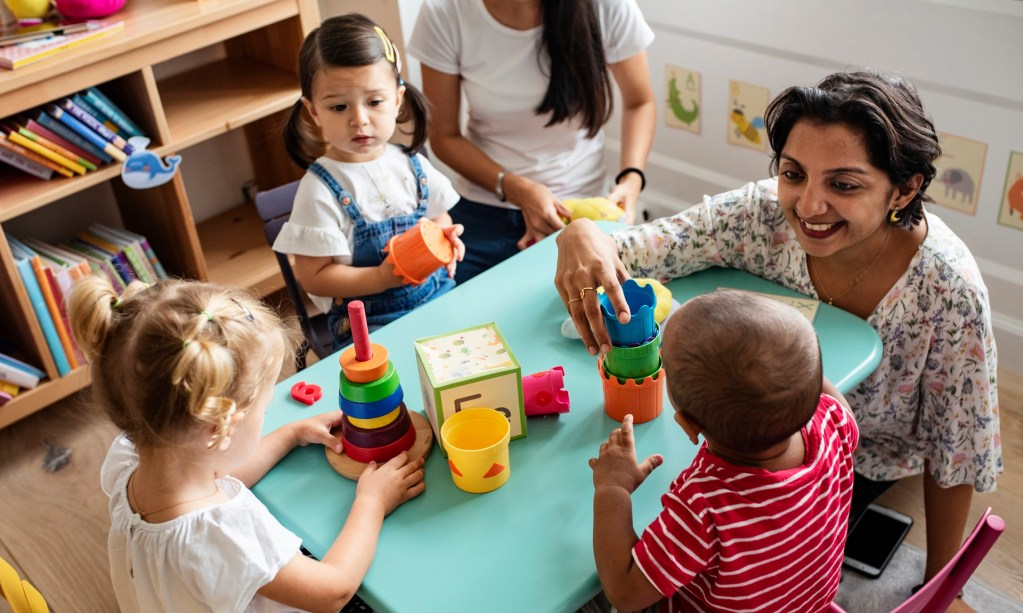 child care worker plays with young children at a day care