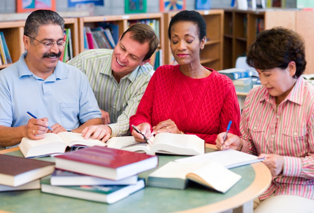teacher helping newcomer students to learn English in a library