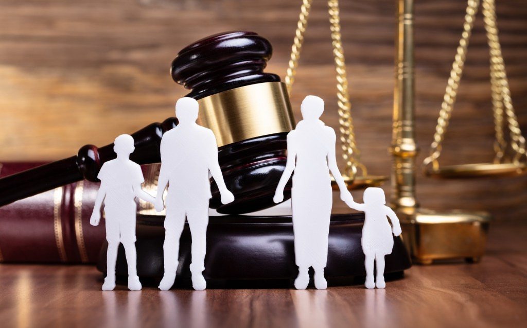 family figure cut out in front of a judge's gavel and the scales of justice on a desk