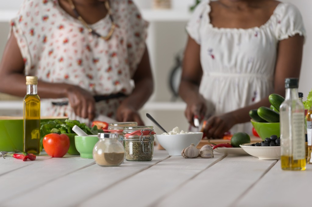 food ingredients on a kitchen counter with women preparing a meal in the background