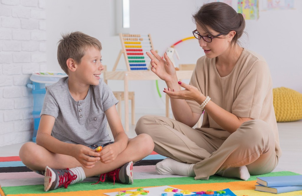 therapist teaches young boy while sitting on floor together