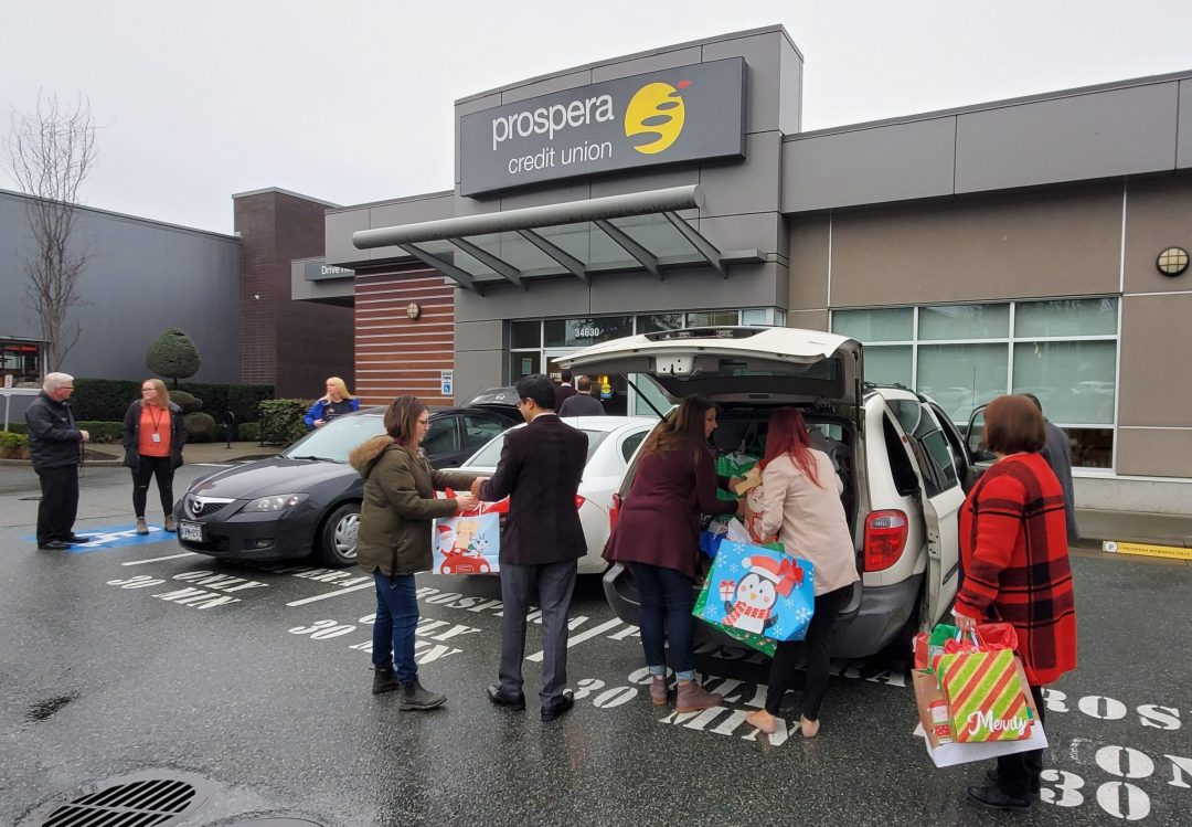 Archway staff collecting gifts from Prospera to deliver to clients of the Youth Angel Tree project