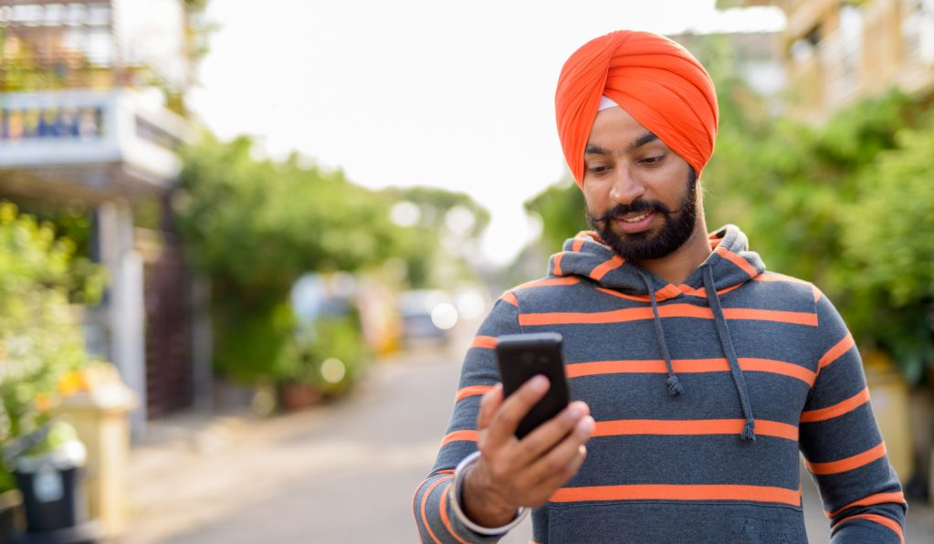 young indian Sikh man using his mobile phone