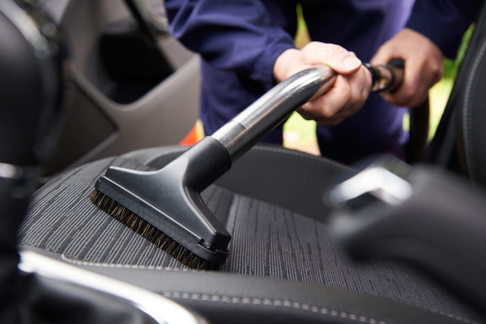 a man is cleaning the seats of a car with black interior