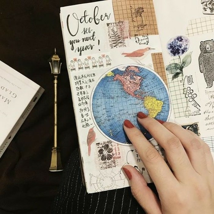 adventure journal, sketchbook with various cutouts, globe map, bear, birds, flowers, stamps, black writing, held by woman's had with red nail polish