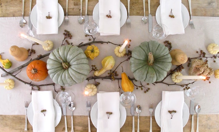 beautiful thanksgiving pictures, white tablecloth on light wooden table, six white plates with white napkins and little berry ornaments, silver cutlery, clear whine glasses, three lit tall candles inside little pumpkins, two large light blue pumpkins, small pumpkins, gourds, two decorative tree branches