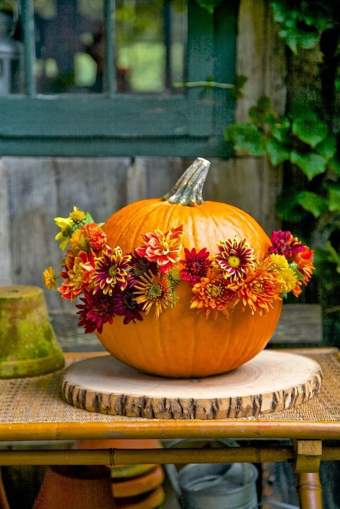 orange pumpkin, adorned with red, yellow, orange and green flowers, placed on a wooden mat, on a garden table, near planting pots, green window, plant and planks in the background
