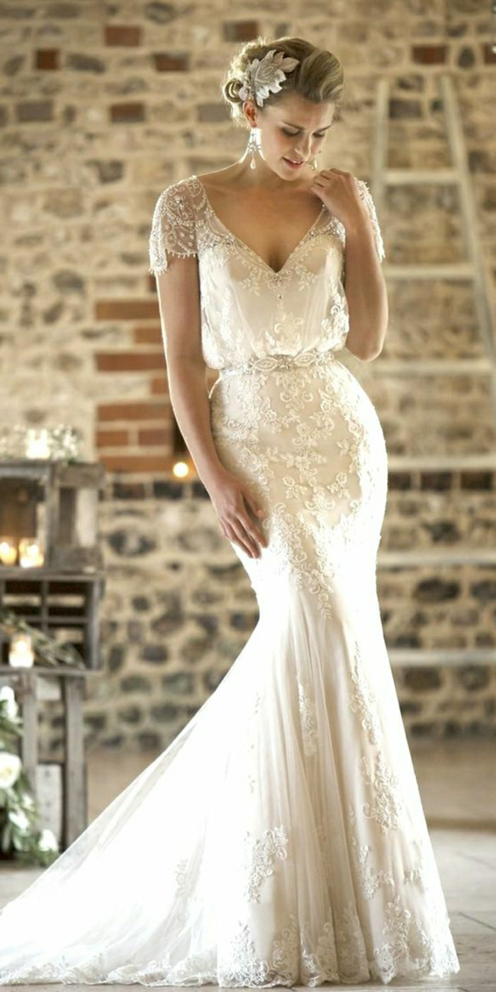 vintage inspired wedding dresses,young blonde bride looking down, wearing embroidered long white dress with lace sleeves and a hair ornament, brick wall and furniture in the background