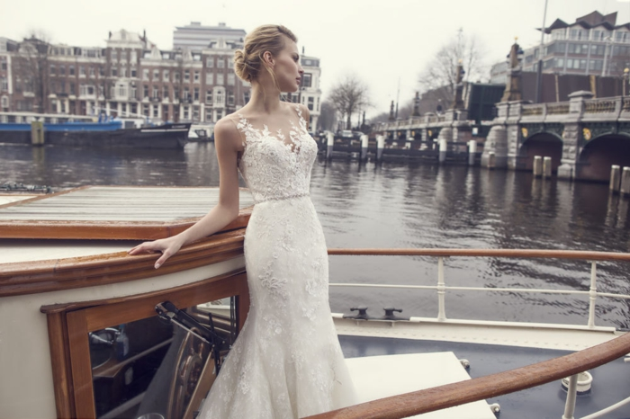 vintage wedding dresses, blonde bride on a boat sailing on the river Seine, wearing long white figure-hugging wedding dress with applique details and lace
