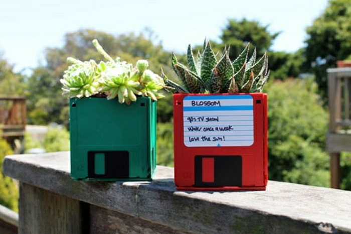 plant pots made to look like floppy disks, placed on a ledge, in green and red, green garden background