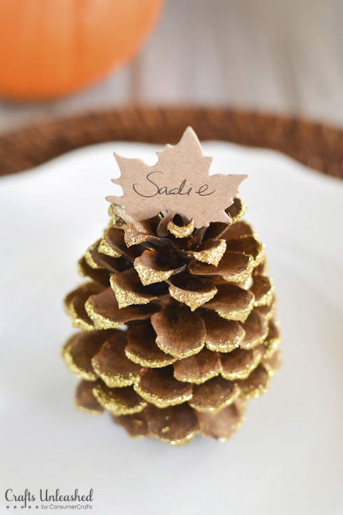 cute happy thanksgiving images, a pine-cone, painted with glittering gold paint, adorned with a paper leaf name card, placed on a white plate, sitting on a wooden mat on a table,