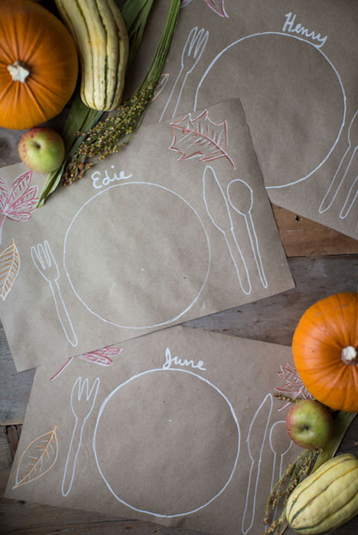 cute happy thanksgiving images, sepia paper mats, with drawings and names written by kids, on a wooden table, near pumpkins, gourds, apples and green plants