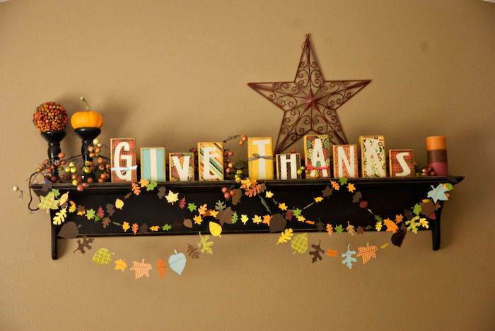 differently sized colorful wooden blocks spelling out give thanks, placed on a dark wooden shelf, adorned with a colorful candle, a round ornament, a small pumpkin and bright colorful garlands made of small paper leaves, on a light orange wall with a brown metal star