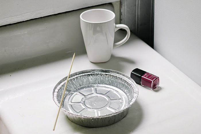 diy gift ideas, white mug placed on a table, near a bottle of dark red nail polish and a tin foil bowl with a wooden skewer