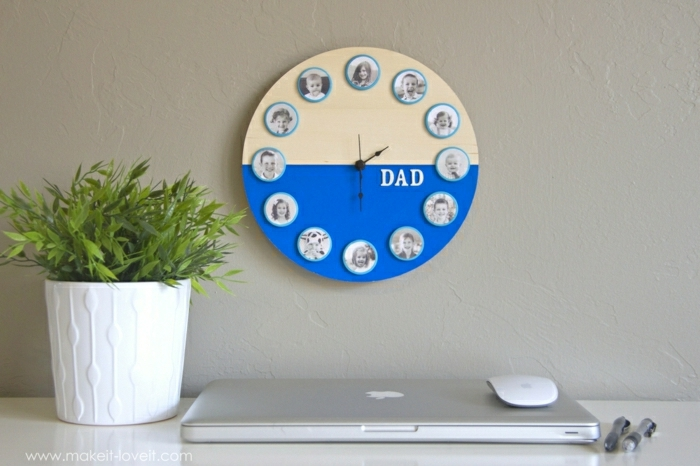 dyi gift ideas, round yellow and blue wall clock with family photos, hanging on a light cream wall, near a potted plant, laptop, mouse and two pens