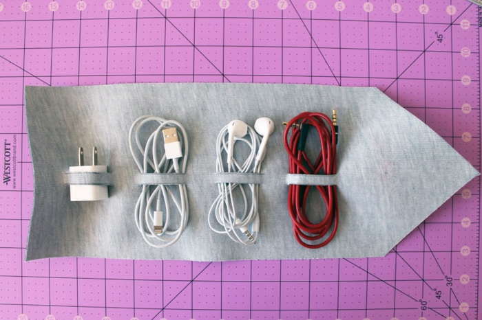 father's day craft ideas, a charger, headphones, USB cable, additional red cable placed in the hoops of the leather organizer, pink cutting mat in the background