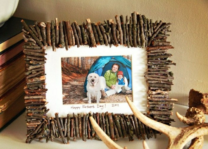 father s day gifts from daughter, photo frame made from twigs, containing a photo of a father, daughter and dog camping in the woods, on a desk, near books and nature-inspired ornaments