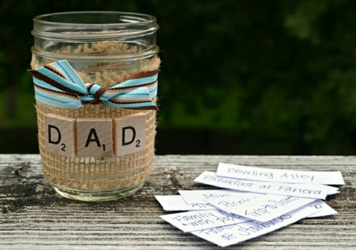 father's day homemade gifts, decorated jar with blue and brown ribbon, pieces of paper, placed on a wooden table, dark background