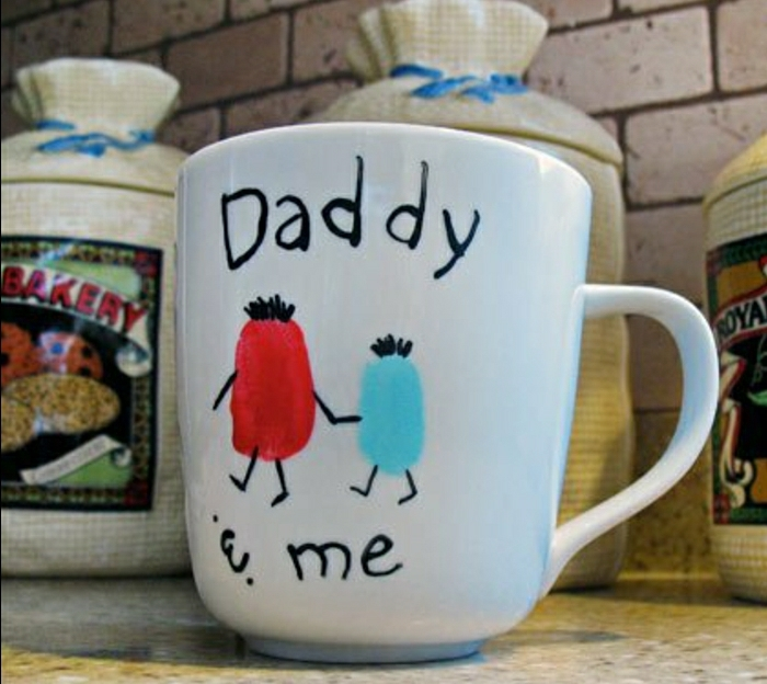 "handmade gifts for dad, white hand painted mug with an orange and a blue shape holding hands, a writing saying ""Daddy an me"", kitchen background"