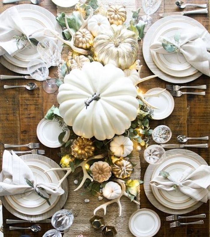 happy thanksgiving pictures, wooden table, white plates on white wooden mats, white napkins, silver cutlery, crystal wine and water glasses, burlap tablecloth, large white pumpkin, smaller pumpkins in gold and white, white antlers, green leaves decoration