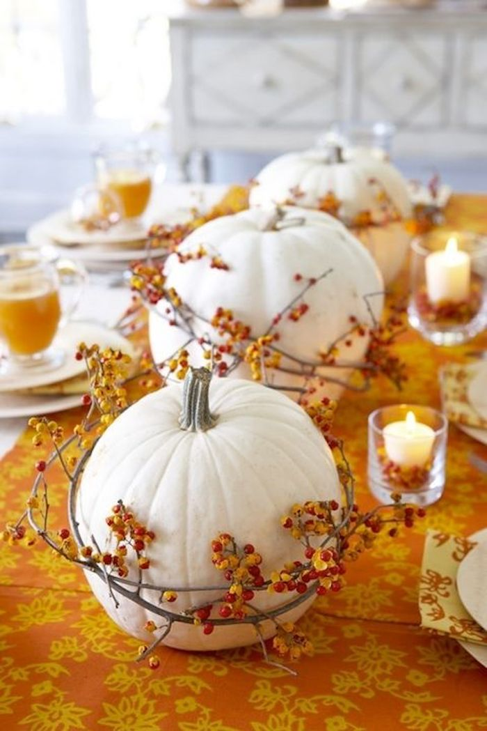 three white pumpkins, with wreaths made of twigs with orange berries, on a table with an orange and yellow tablecloth with white plates, glasses filled with orange juice and two small lit candles in clear glasses, white cabinets and window in the bakground