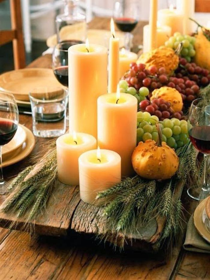 happy thanksgiving pictures, lit candles in different shapes and sizes, placed on a rough wooden aboard, next to grapes, green wheat bunches, gourds, little pumpkins, on a wooden table with plates, full wine and water glasses