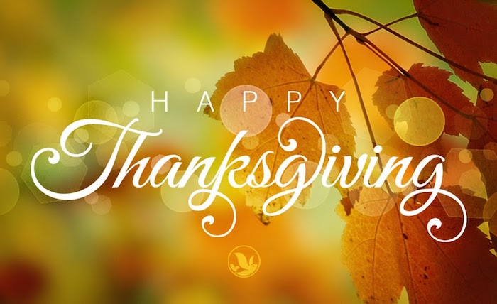 images of thanksgiving, happy thanksgiving in white writing, on a blurry green, orange and yellow background with a branch with orange leaves