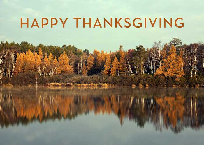 images of thanksgiving, forest in autumn with orange and green trees, blue sky with clouds, all reflected in a lake, brown writing saying happy thanksgiving