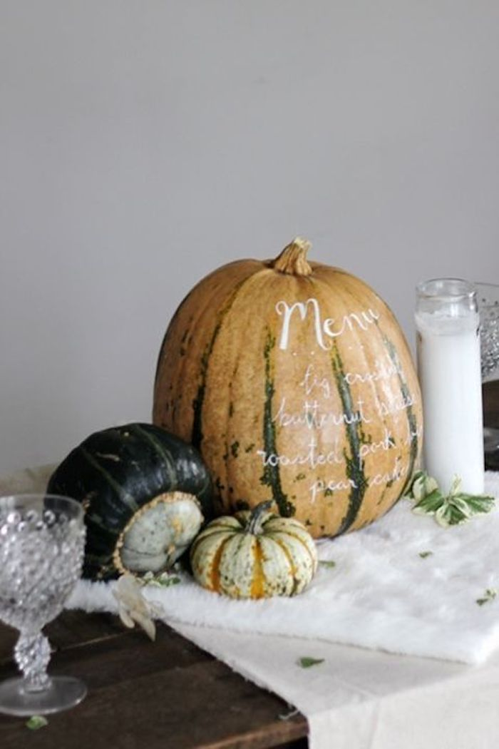 large orange and green pumpkin with a dinner menu written in white, two smaller pumpkins in light and dark green, all placed on a white table cloth, on a wooden surface with two crystal glasses and a large white candle