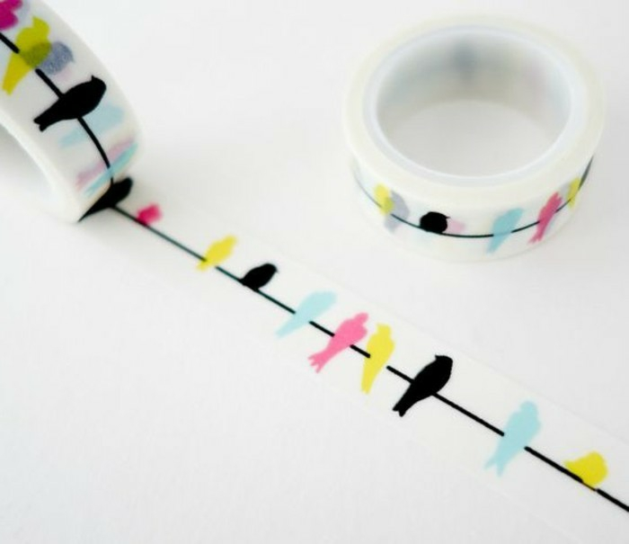 scrapbook ideas for beginners, two rolls of white sticky tape with yellow, black, blue and pink bird design on white background
