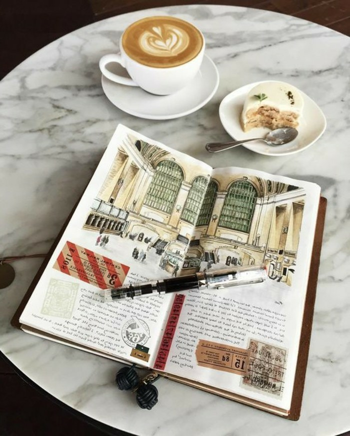 scrapbook layouts, sketchbook with colorful drawing, old travel tickets, white coffee cup with latte, a dessert, plates, pen, marble table