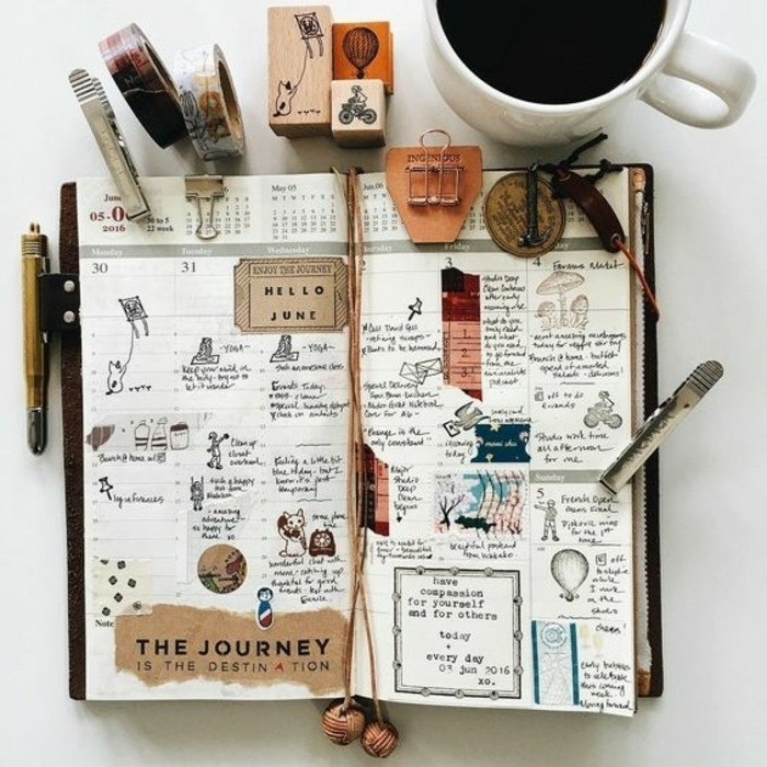 scrapbook ideas, organizer, journal with calendar, dates, months, cutouts, tickets, drawings, writing, near full coffee cup, stationary