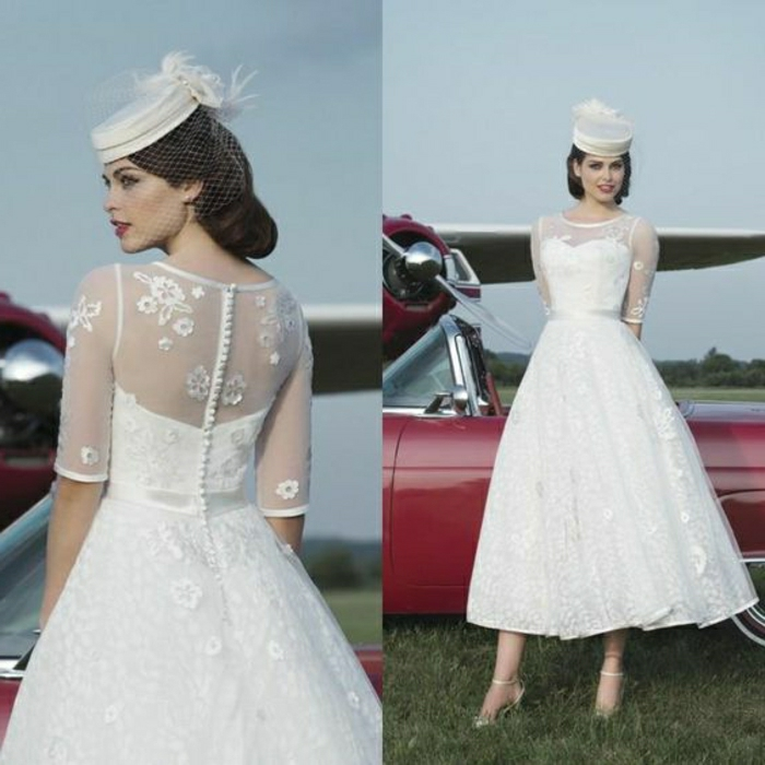 tea length wedding dresses, two images of a woman facing back and front, wearing a 1950s style tea length dress with lace and embroidery, small white cap with feather, standing in front of a retro car and a small plane