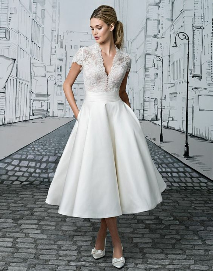 short lace wedding dress, blonde woman with hands in pockets looking down, wearing a white call-length wedding dress with lace and white shoes with bows, drawing of a city in background