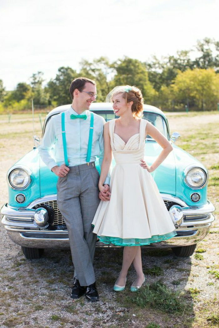 short white wedding dresses, a man with glasses in white shirt and turquoise bow tie and overalls, and a woman in calf-length dress with turquoise petticoat and shoes, holding hands in front of a turquoise retro car