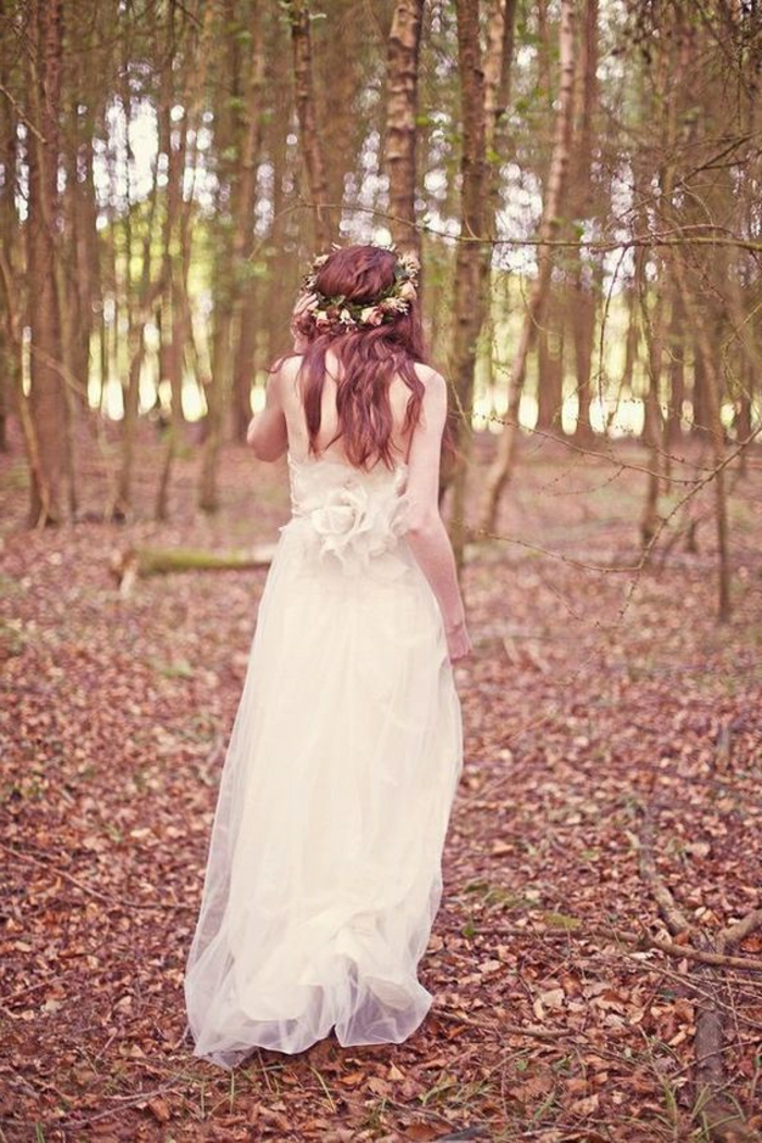 unique wedding dresses, auburn-haired bride in long dress made of tulle, facing backwards and walking in the woods, one hand holding a rose crown on her head, trees, leaves