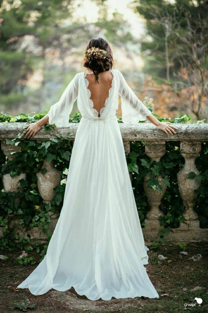 simple wedding dress, woman in long white dress with wide sleeves and an open back, leaning on a terrace made of stone with green creeping plants and trees in background, messy hair bun with ornaments