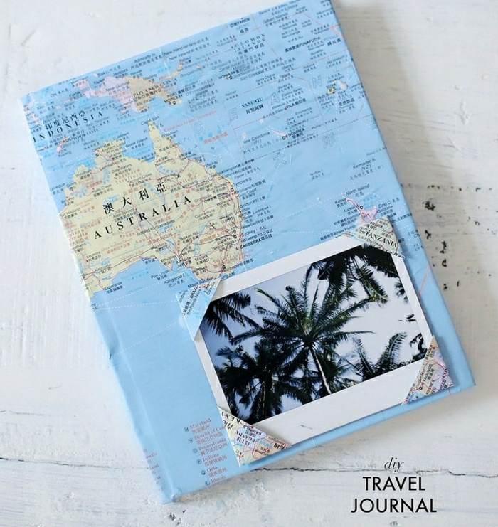 step dad gift ideas, hand decorated travel journal, made with a world map, on a white wooden table, with a palm tree photo stuck on the cover