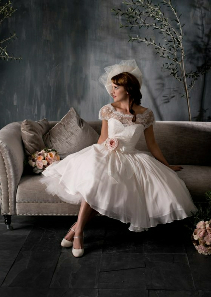 tea length wedding dresses, brunette woman in bridal dress and hat sitting on a grey couch, lace details and a pink rose on her belt, two bouquets of roses, grey background with small decorative tree