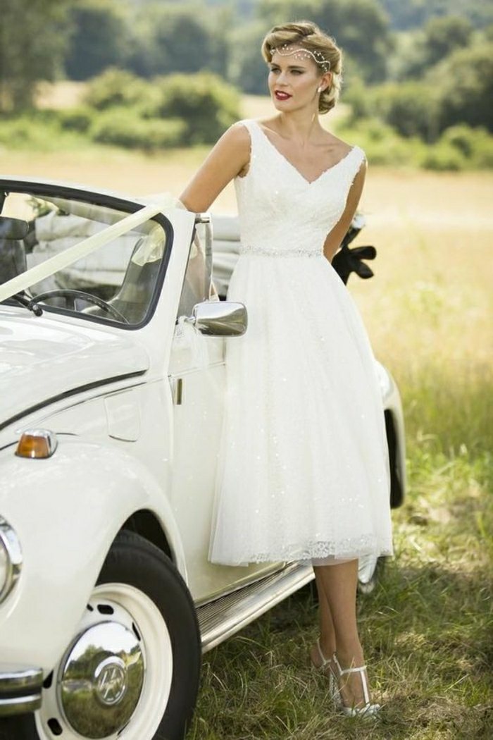 tea length dresses, fair-haired woman in simple wedding dress, with vintage-inspired hairstyle and a forehead tiara, leaning on a white retro car with bow, green fields in background