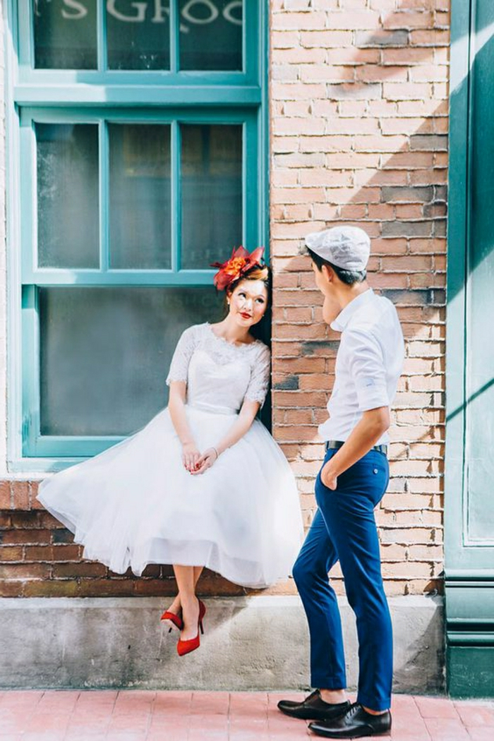 short white wedding dresses, young bride with simple white dress red shoes and red hair ornament, sitting on a window sill and looking at a young man in jeans, white shirt and grey cap