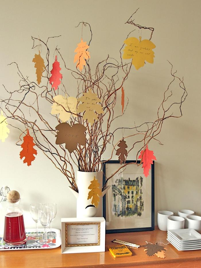 thanksgiving photos, dried tree branches, adorned with yellow, orange and brown leaf-shaped cutouts with messages, in a white vase, on a wooden table, with pitcher of juice and glasses on a tray, white coffee cups and square plates and two frames