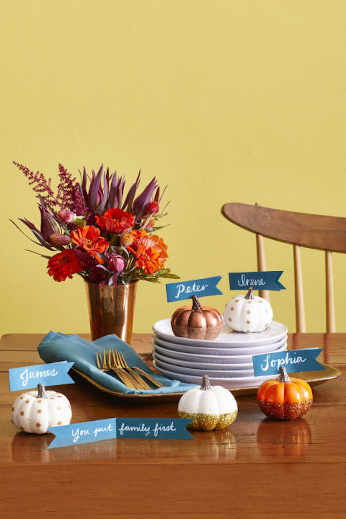 thanksgiving photos, little painted pumpkins in various colors, with blue name tags attached to their stems, on a brown wooden kitchen table, featuring several white plates and a blue napkin with silver forks, on a tray, near a golden vase with red autumn flowers, chair, yellow background