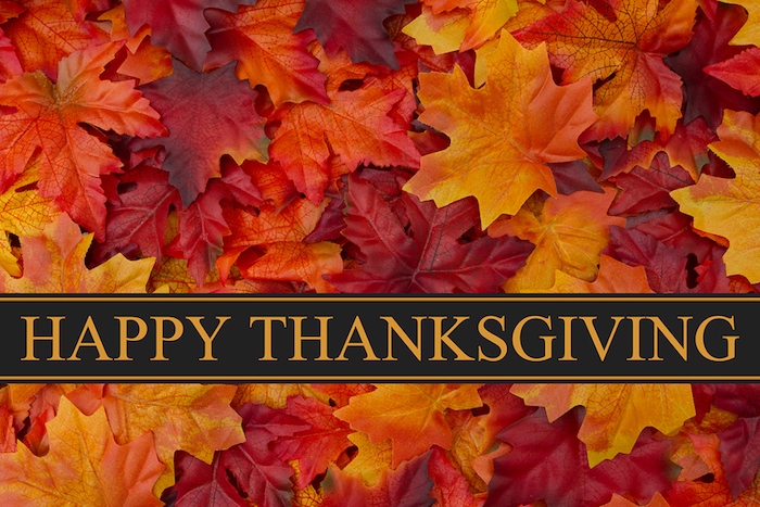 thanksgiving pictures, many dark red, orange and yellow leaves with a black banner saying happy thanksgiving in yellow writing