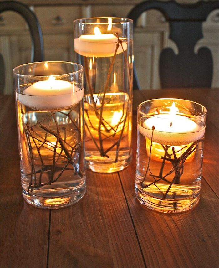 glasses of different sizes filled with water and twigs with lit floating candles inside, on a wooden table with two chairs and white cabinets in the background