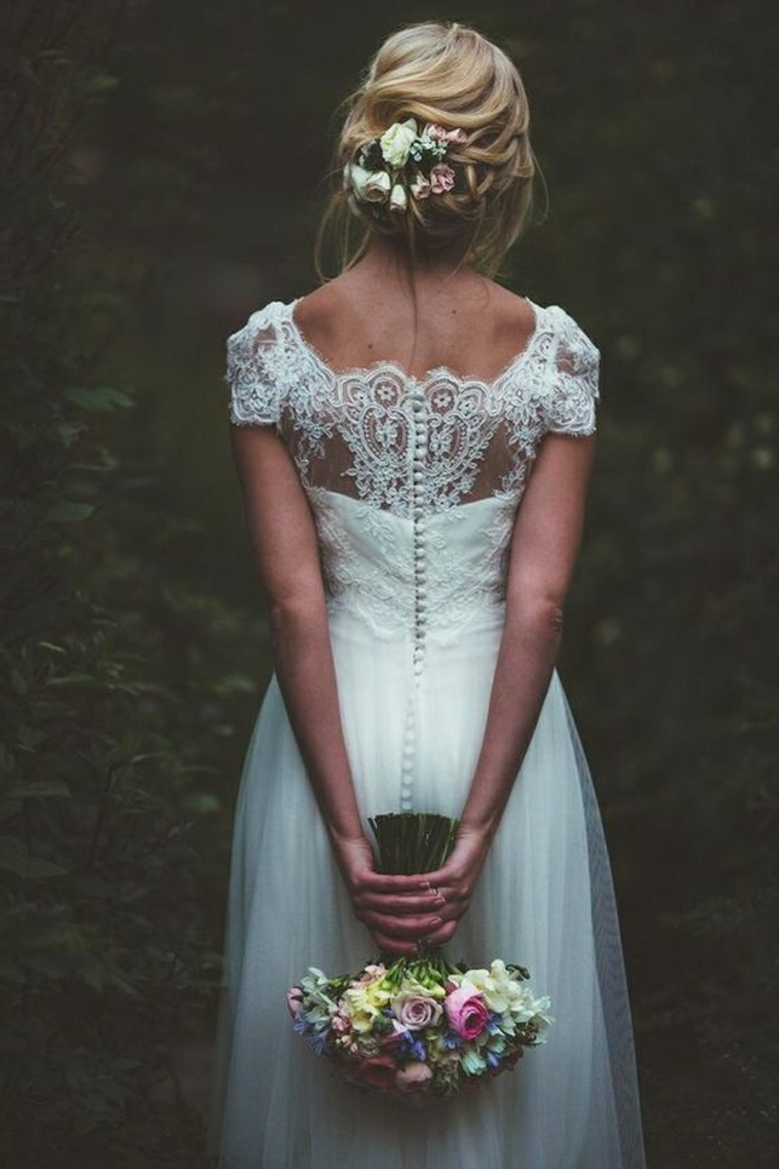vintage wedding dresses, blonde bride with flowers in hair facing backwards, wearing a long white bridal dress with lace back and buttons, holding a bouquet of flowers, dark forest background