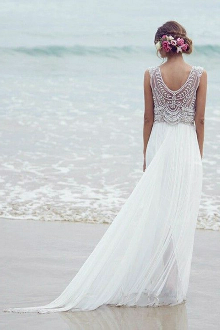 simple wedding dress, woman in long white dress with pleats and a lacy embroidered back, standing on a sandy shore in front of the sea, formal up-do with flowers in hair