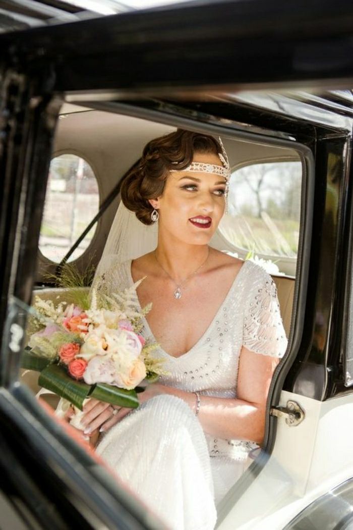 vintage inspired wedding dresses, bride with 1920s clothes hair and headband sitting in old-fashioned car and holding flowers